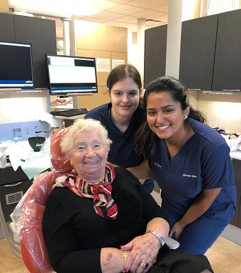 Dental students Shreya Jha and Nicole Zimmerman with 94-year-old patient and Holocaust survivor Leah Cik Roth.